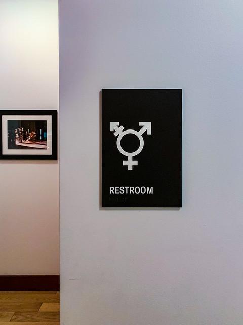 2019.03.05 DC People and Places, Washington, DC USA 7422, une image de Ted Eytan (cc by-sa 2.0). L'image montre un signe pour les toilettes s'adressant aux personnes de tous les genres et non-binaires ou agenrées.