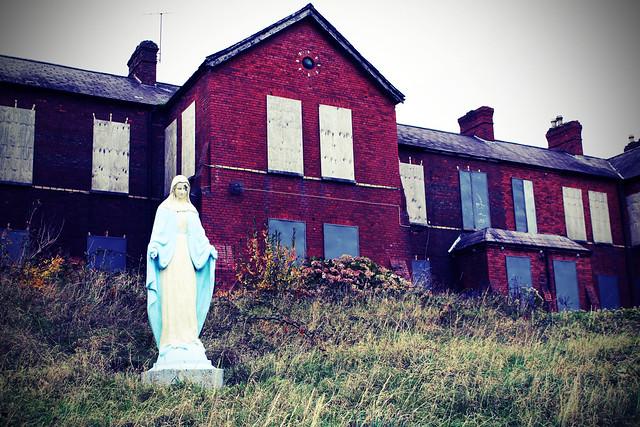 • Mary, une photo de Alison Killilea (cc by-nc-nd 2.0). L'image montre un ancien hôpital dont les fenêtres et portent sont barricadées. Devant, il y a une statue de Marie.