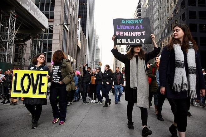 """Image sans titre de Alec Perkins (cc by 2.0). On y voit des femmes pendant la marche des femmes de New York en 2018. À gauche, une femme porte un pancarte sur laquelle est inscrit """"Love""""; à droite, une autre femme, une pancarte sur laquelle est inscrit """"angry liberal feminist killjoy""""."""