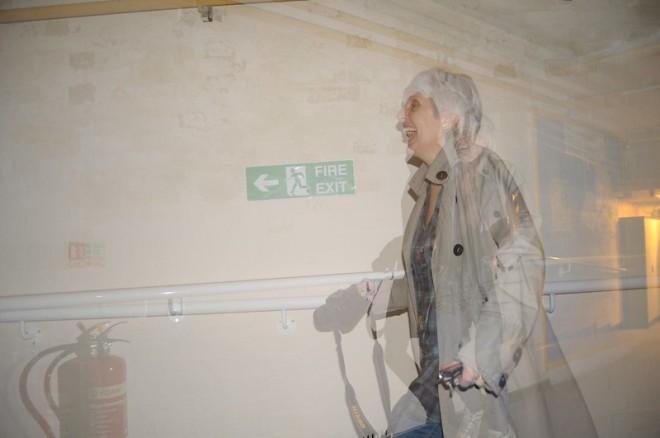 Une femme marche dans un corridor, rigolant. Une surimpression donne un effet fantôme.