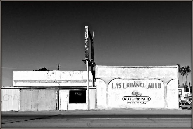 Image d'un garage commercial fermé (plusieurs fenêtres sont placardées, l'enseigne n'est plus). Sur un des murs est écrit: «Last Chance Auto; Auto Repair; We Do it All!».