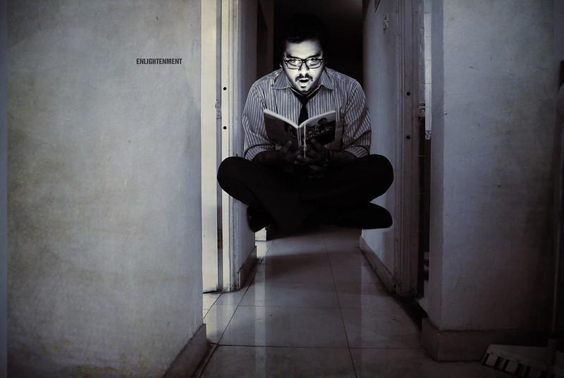 Un homme assis en tailleur tient un livre à la main, son visage illuminé et son expression intéressée. Il lévite à quelques dizaines de centimètres du sol. Sur un mur à la hauteur de sa tête, un mot: enlightenment.