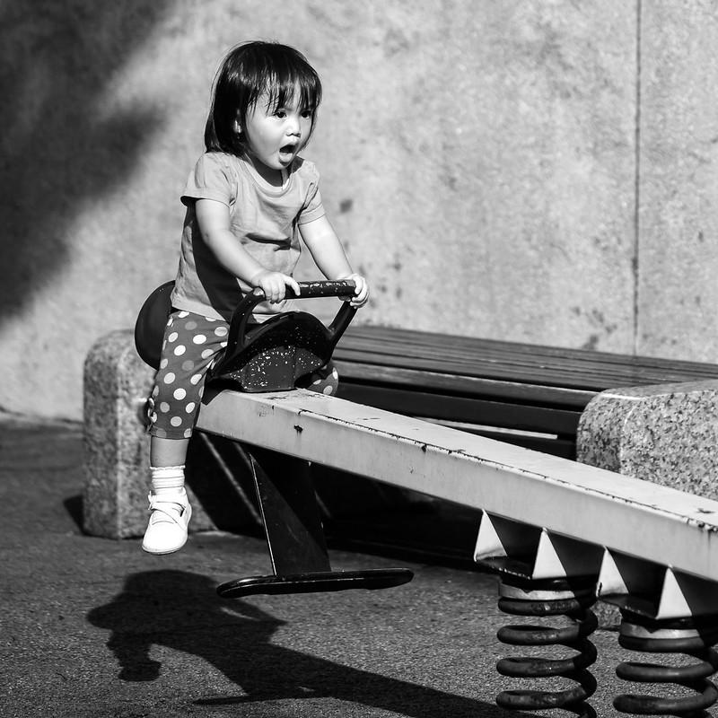 Une fillette est assise sur un jeu dans un parc, on ne sait si l'expression de son visage exprime un bon ou un mauvais moment.