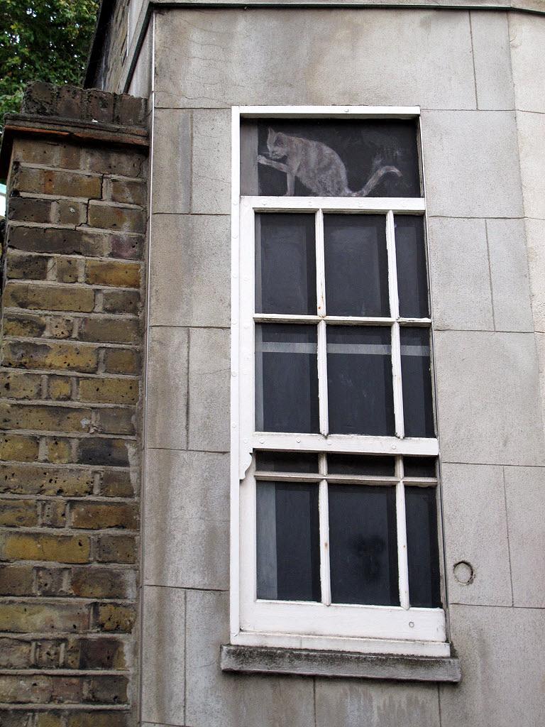 Dans le haut d'une fenêtre, un dessin donne l'impression qu'un chat se tient sur le cadre.