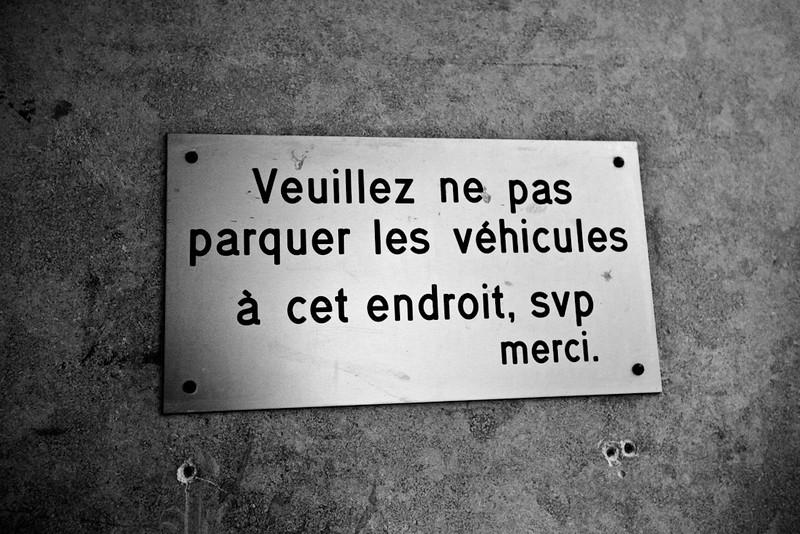 """Une plaque sur un mur se lit comme suit: """"Veuillez ne pas parquer les véhicules à cet endroit, svp merci."""""""