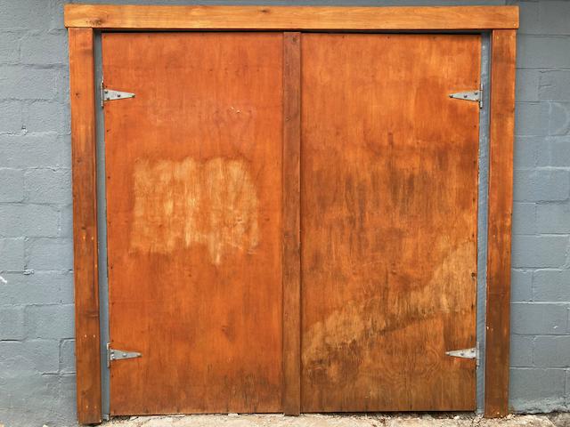 Deux portes de garage en bois de couleur cuivre intense entourée de brique grise.