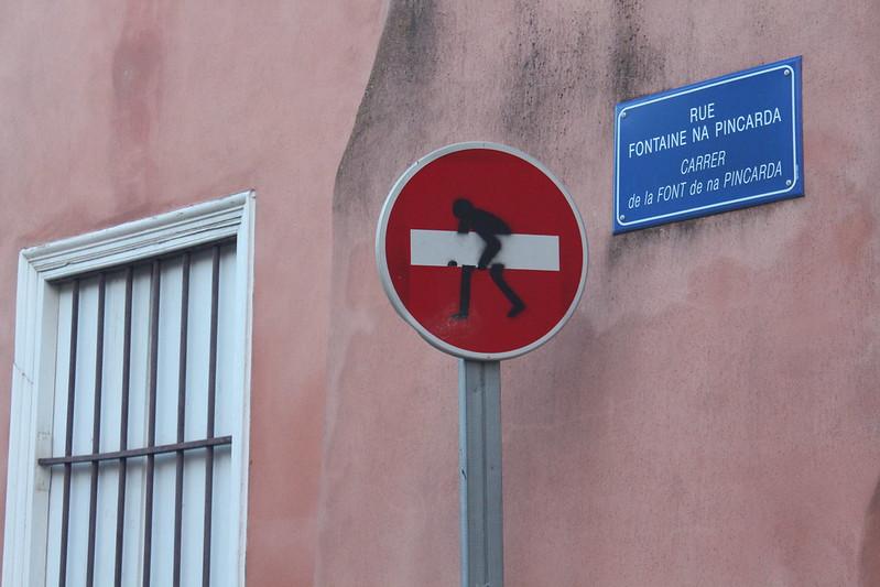 Sur un panneau routier de sens interdit, un personnage a été dessiné, il semble porter la bande blanche du panneau sous le bras en avançant.