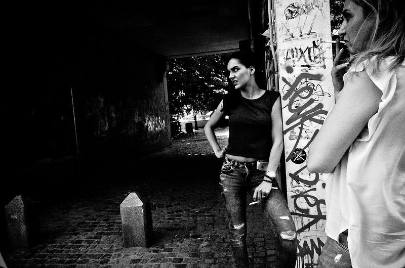 À l'entrée d'un passage, deux jeunes femmes se grillent une clope, regardant toutes les deux dans une même direction, l'air méchant.